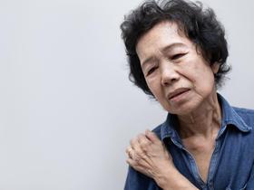 Senior Asian woman holding painful shoulder