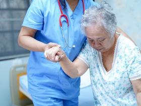 Elderly woman being helped