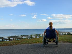Young woman in wheelchair looking at view of sea
