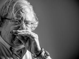 Black and white picture of James Allison playing the harmonica
