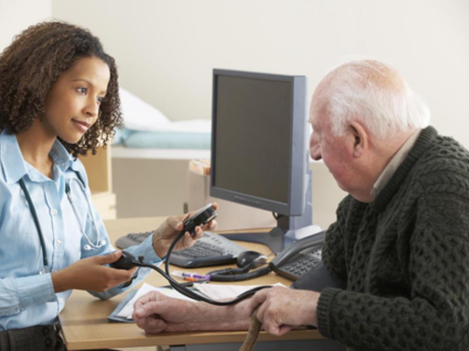 young female doctor taking elderly man's BP