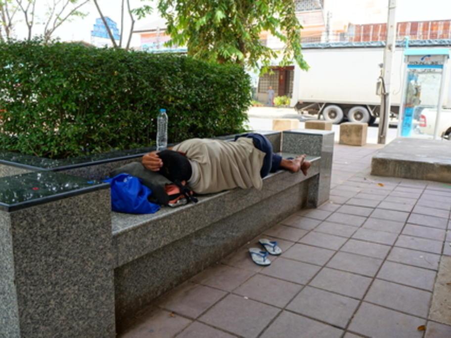homeless man sleeping on city bench