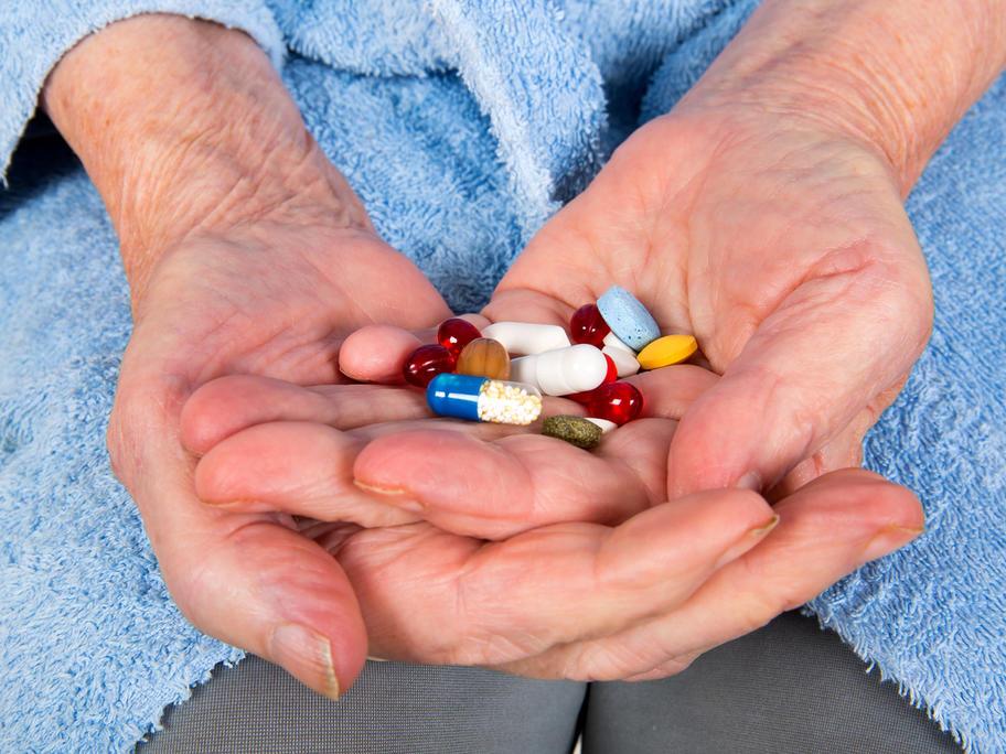 Elderly hands holding lots of medication