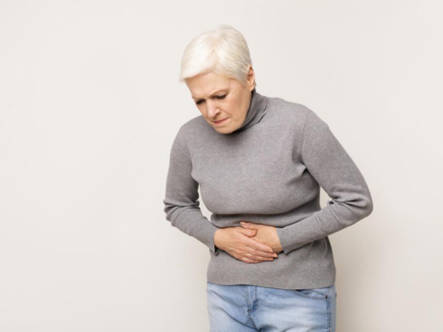 anxious senior woman clutching her abdomen