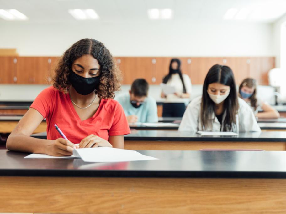 People wearing masks while taking exam