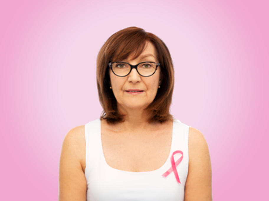 postmenopausal woman against pink background wearing ribbon