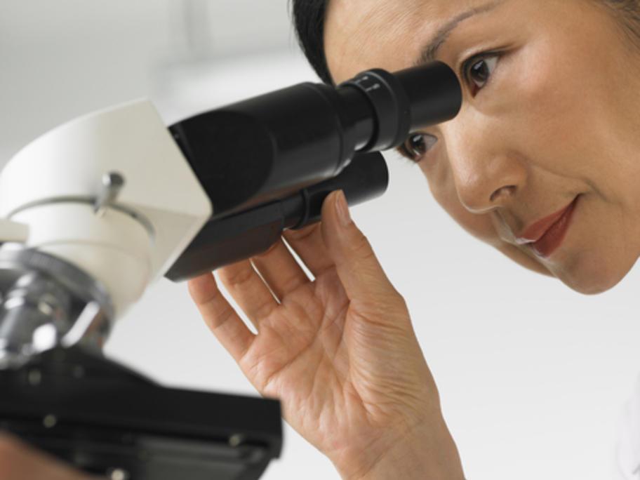 female pathologist looking down microscope