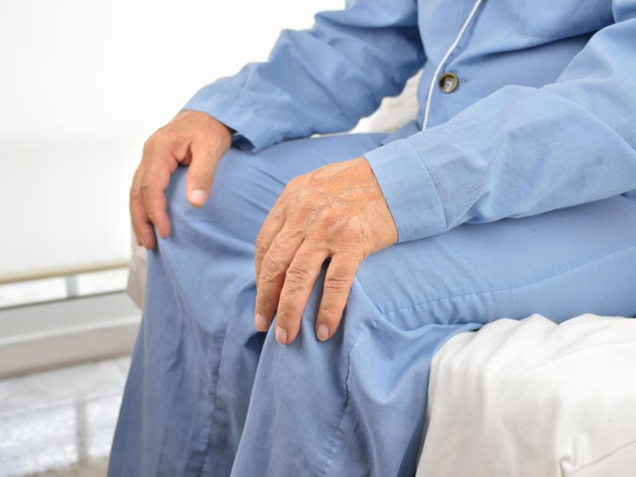 old man in pyjamas sitting on hospital bed