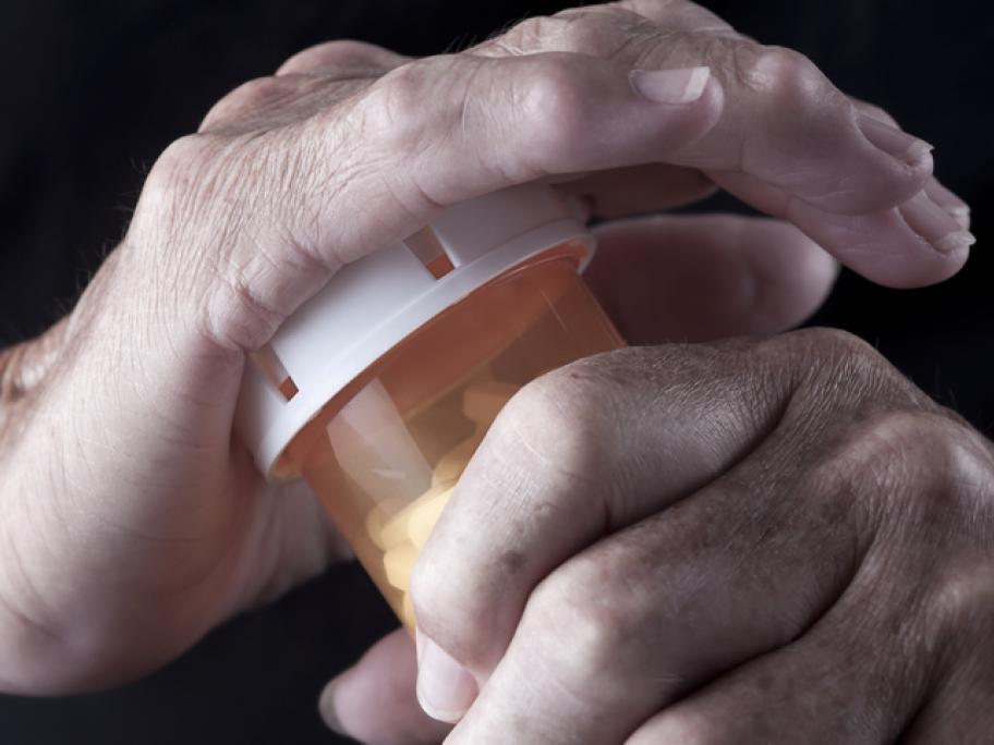 arthritic hands opening a pill bottle