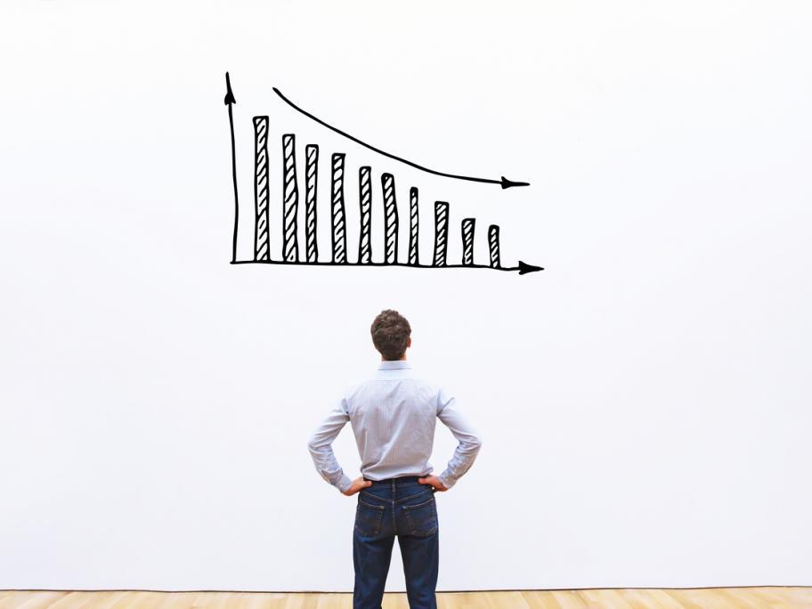 man looking at decreasing graph on white wall