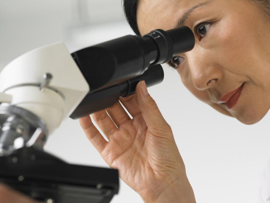 woman looking down microscope