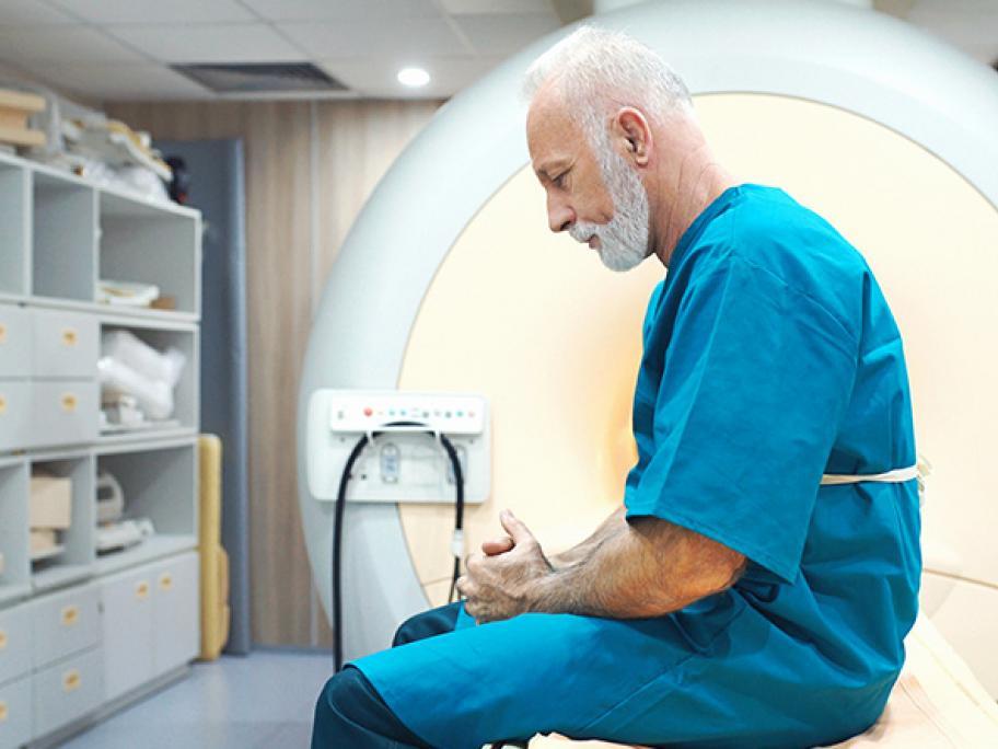 Senior man looking worried sitting in front of MRI scanner